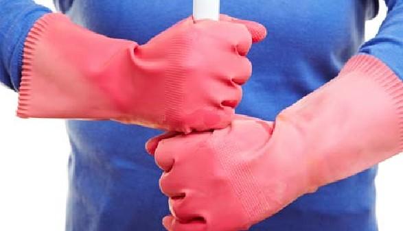 Reinigungskraft hält Besen mit Gummihandschuhen © Robert Kneschke, Fotolia.com