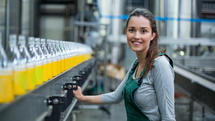 Junge Frau steht beim Fließband mit Getränkeflaschen © WavebreakMediaMicro, stock.adobe.com
