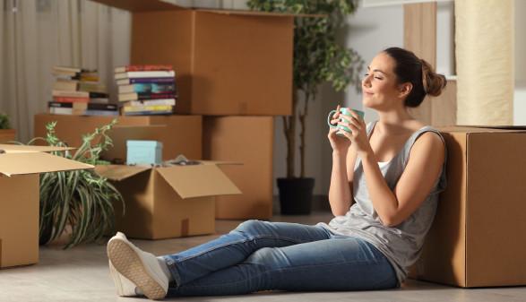 Junge Frau sitzt am Boden rundherum Umzugskartons © Antonioguillem, stock.adobe.com