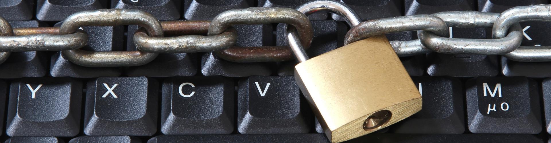 Eine Kette mit Vorhängeschloss spannt sich quer über eine Tastatur. © Björn Wylezich, stock.adobe.com