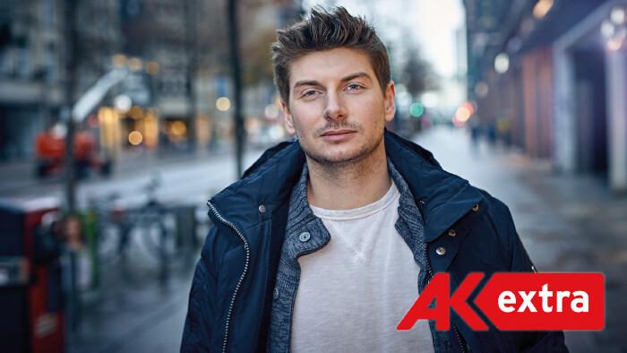 Junger Mann in Winterjacke steht auf einer Straße und schaut in die Kamer © Uwe Krejci, shutterstock.com