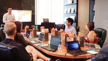 6 Menschen sitzen um einen Verhandlungstisch vor ihren Laptops und hören einer Präsentation zu © Unsplash - Campaign Creators