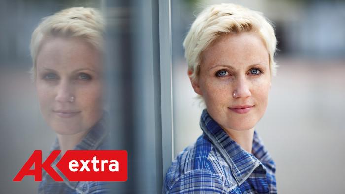 Blonde, kurzhaarige Frau mit blaukariertem Hemd steht vor spiegelndem Hintergrund undschaut in die Kamera © stockfour, shutterstock.com