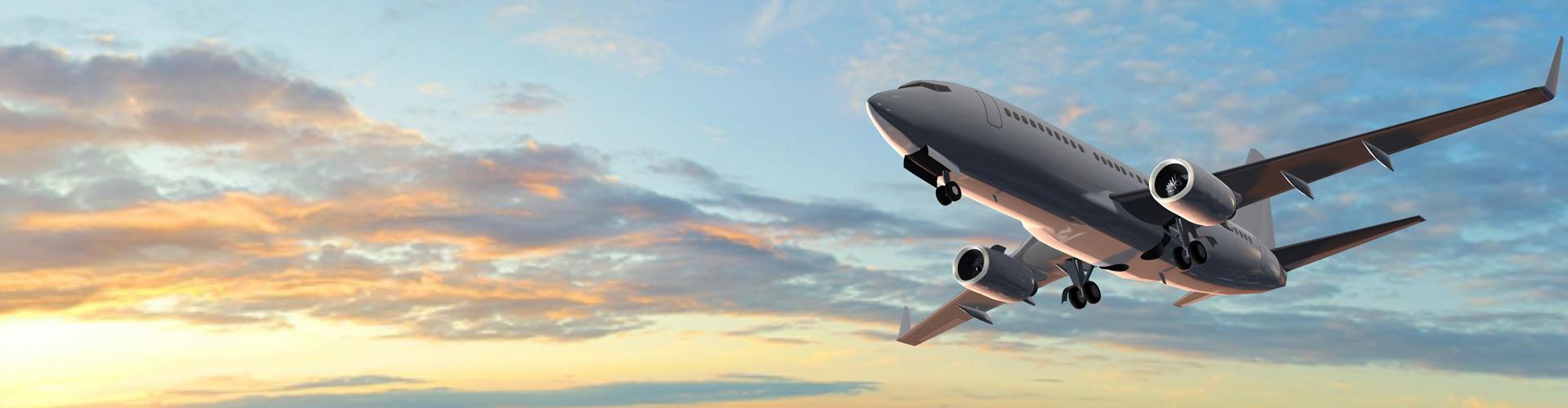Vor einem leicht bewölkten Himmel mit Morgenrot sieht man ein Passagierflugzeug von schräg links unten. © Riko Best, stock.adobe.com