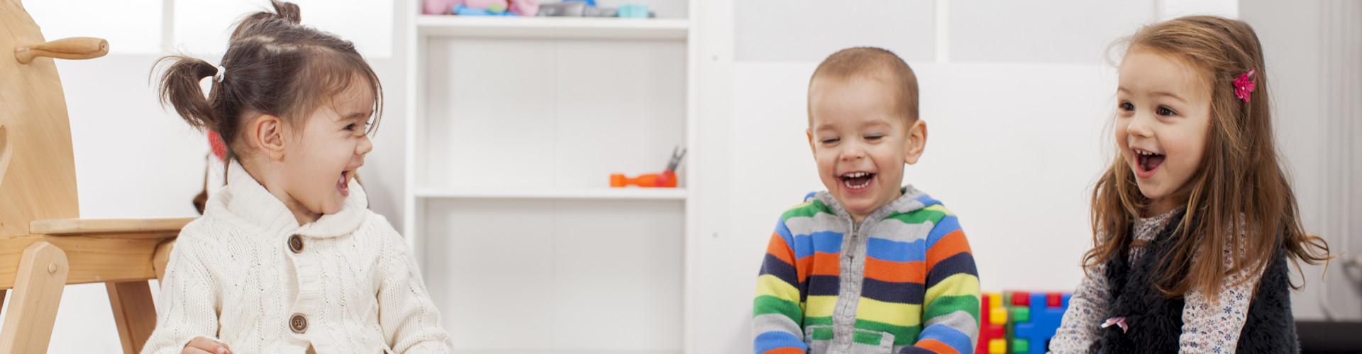 Zwei kleine Mädchen und ein Bub sitzen im Kindergarten und lachen © Boggy, stock.adobe.com