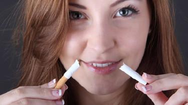 Junge Frau hält zwei Teile einer zerbrochenen Zigarette in den Händen © Knut Wlarda, stock.adobe.com