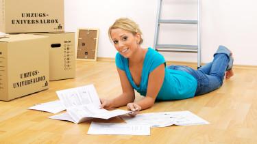 Junge Frau liegt am Boden vor mehreren Umzugskartons und betrachtet einige Dokumente. Im Hintergrund steht eine Leiter an der Wand. © Light Impression, stock.adobe.com