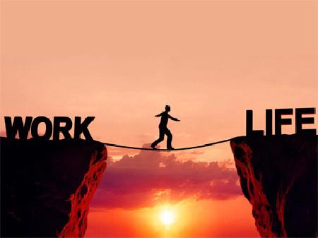 Vor einem Sonnenuntergang sieht man zwei Klippen, auch denen die Worte Work, beziehungsweise Life geschrieben stehen. Zwischen den Klippen ist ein Seil gespannt, auf dem eine Person balanciert. © fotomek, stock.adobe.com