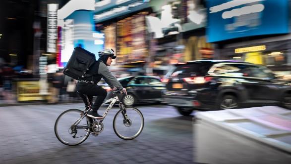 Radzusteller radelt über den im Hintergrund verschommen sichtbaren New Yorker Timesquare © Unsplash - Brett Jordan