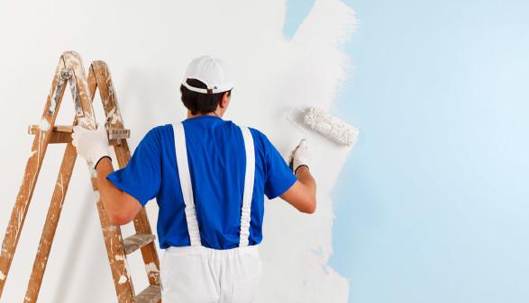 Maler steht auf einer Leiter und malt die Wand aus © guerrieroale, stock.adobe.com