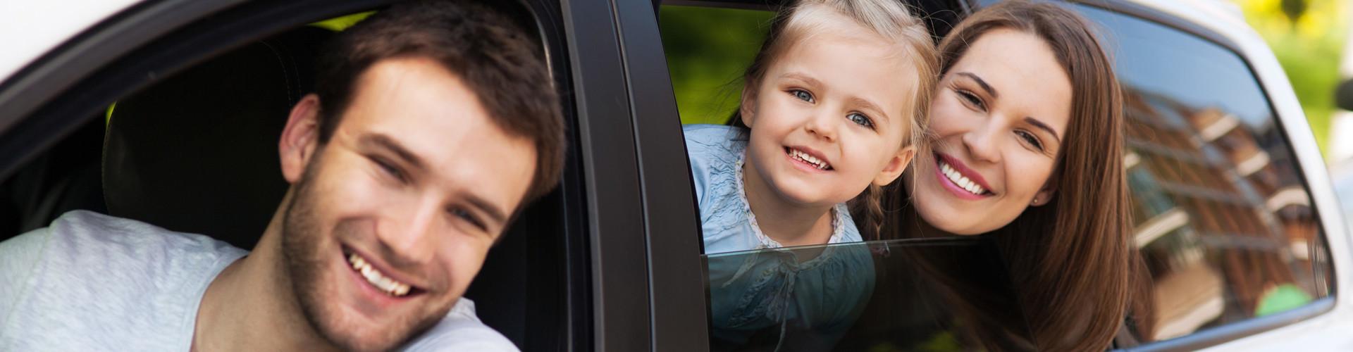 Mann blickt vom Fahrersitz aus dem Fenster eines weißen Autos, Frau und Kind blicken aus dem hinteren Fenster. © pikselstock, stock.adobe.com