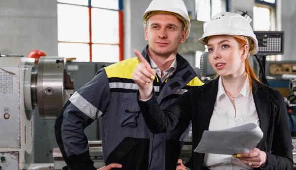 Eine Frau mit Klemmbrett und Bauhelm steht neben einem Mann in Arbeitskleidung und deutet auf einen Punkt außerhalb des Bildes © ProstoSvet, stock.adobe.com
