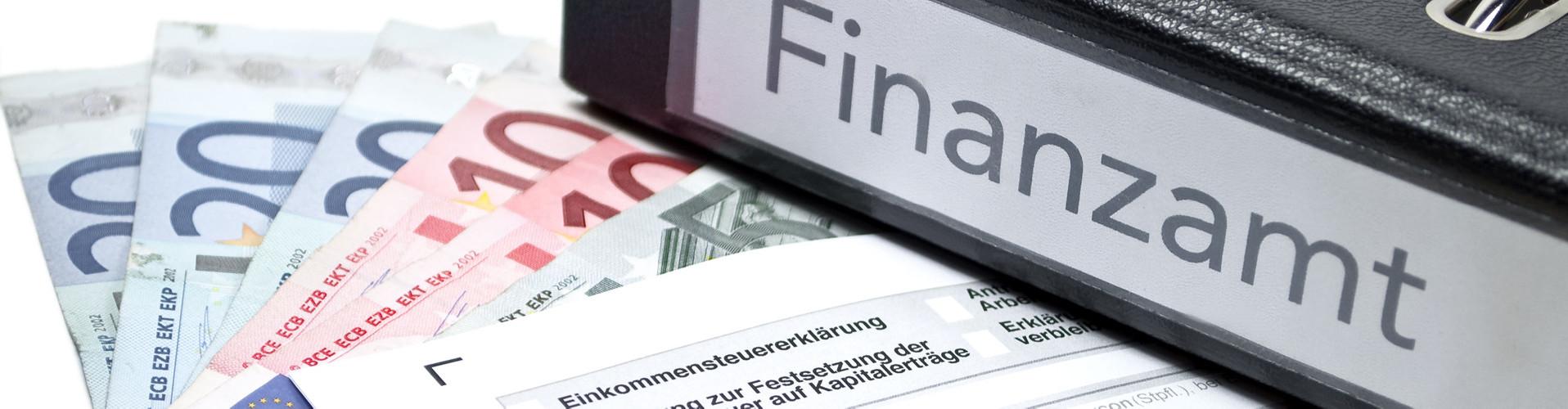 """Auf einem Tisch liegen Geld, eine Einkommensteuererklärung und ein Ordner mit der Aufschrift """"Finanzamt"""" © Stockwerk-Fotodesign, stock.adobe.com"""