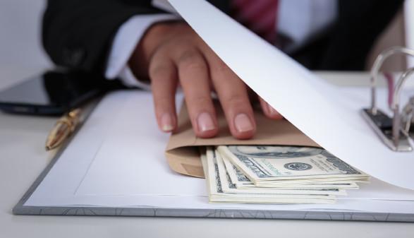 Mann greift nach Geld in einem Kuvert © kamonrat - stock.adobe.com