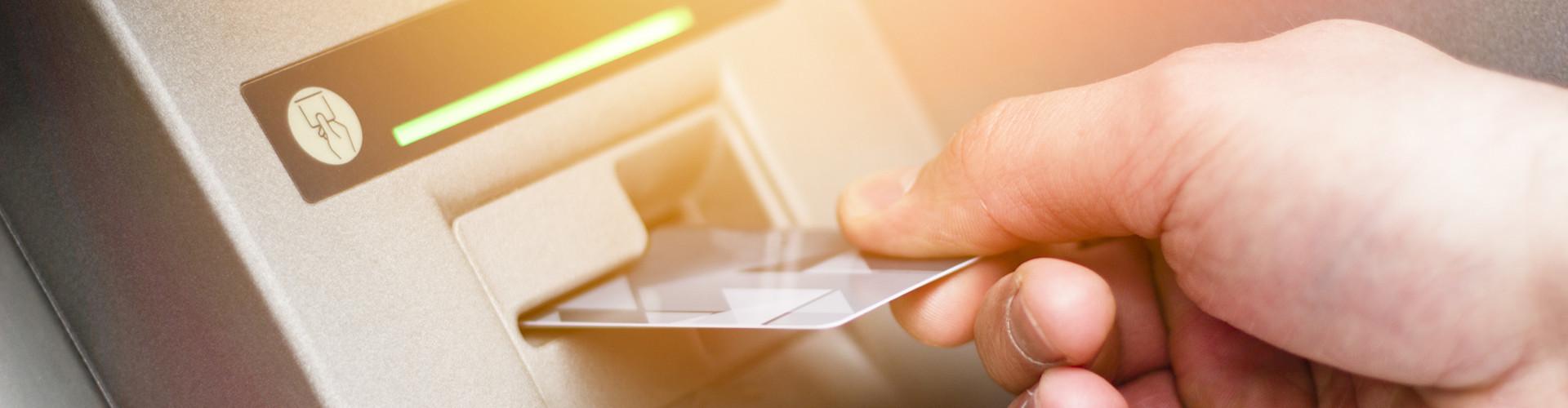 Man sieht die Hand eines Mannes, der eine Bankkarte in einen Bankomaten einführt. © Addoro, stock.adobe.com
