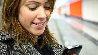 Eine junge Frau blickt konzentriert auf ihr Handy. © benik.at, stock.adobe.com