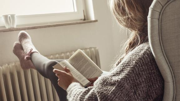 Junge Frau schaut aus dem Fenster, trinkt Tee und legt Füße zum Aufwärmen auf die Heizung  © weixx, stock.adobe.com