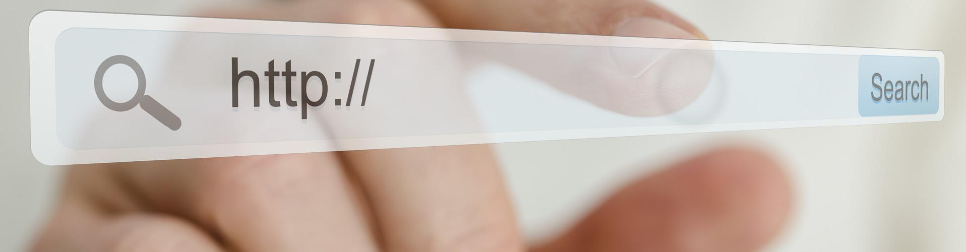"""Man sieht eine transparente Ebene mit einer URL-Zeile, in welcher """"http://"""" geschrieben steht. Im Hintergrund sieht man die Hand eines Mannes danach greifen. © Gajus, stock.adobe.com"""