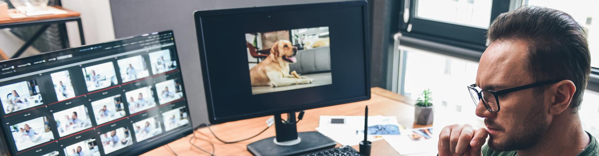 Junger Mann mit Brille sitzt am Schreibtisch, vor ihm stehen zwei Bildschirme © YakobchukOlena, stock.adobe.com