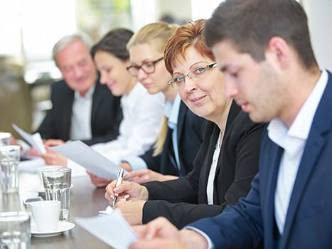 Frauen und Männer im Businessoutft sitzen in einer Reihe an einem Tisch bei einem Meeting, eine Frau schaut direkt in die Kamera. © Robert Kneschke, Fotolia.com