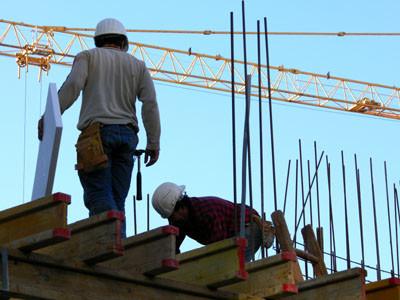 Bauarbeiter arbeiten auf einer Baustelle am Dach. © artpost, fotolia.com