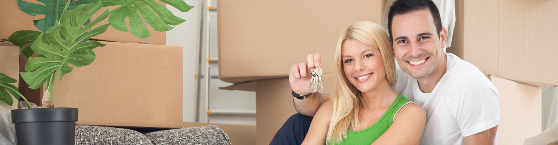 Junges Paar sitzt am Boden seiner neuen Wohnung. Der Mann hält den Schlüssel in die Höhe, im Hintergrund stehen Umzugskartons und eine Zimmerpflanze. © luckybusiness, stock.adobe.com