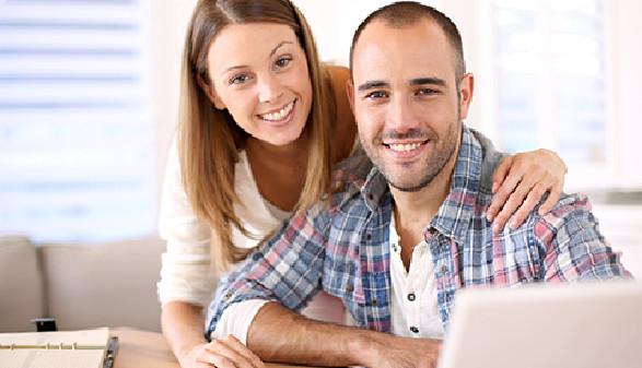 Paar vor Laptop mit Taschenrechner © Goodluz, Fotolia.com