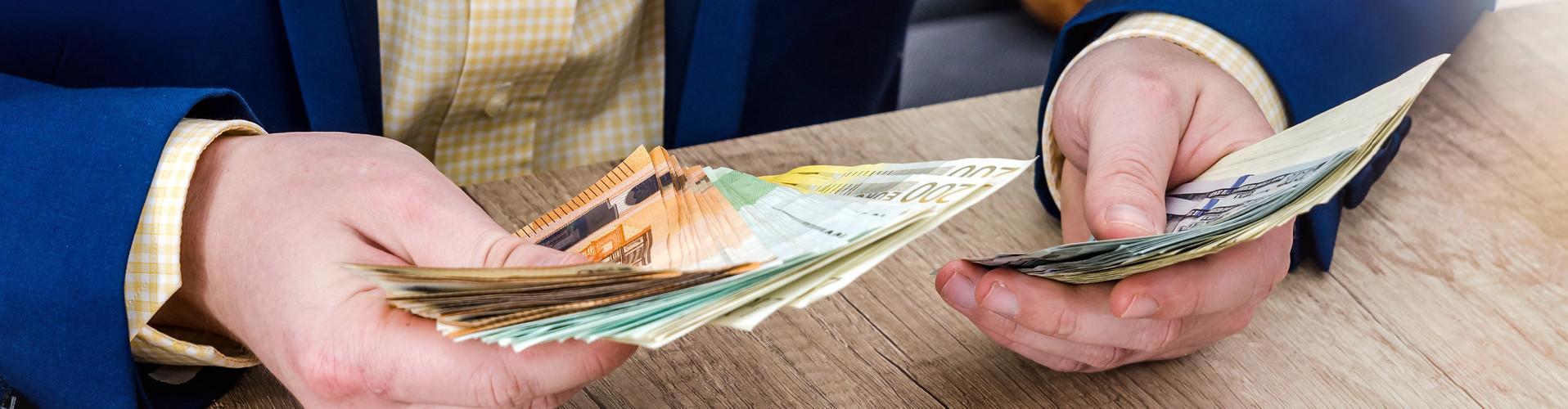 Blick auf die Hände eines Mannes im Anzug, der Geld zählt © alfexe, stock.adobe.com